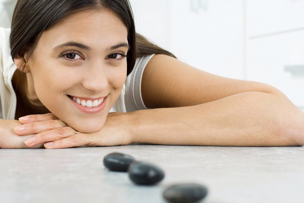 Stock Photo: 1747R-10626 Young woman lying on stomach, resting head on arms, behind small black stones in a line