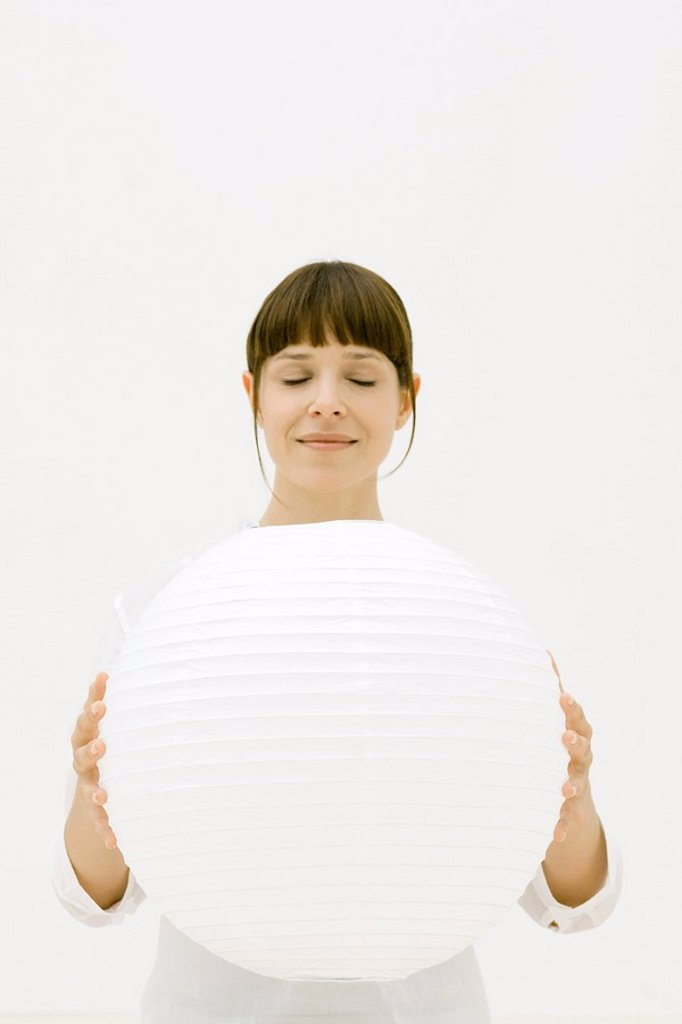 Woman holding large sphere, eyes closed : Stock Photo