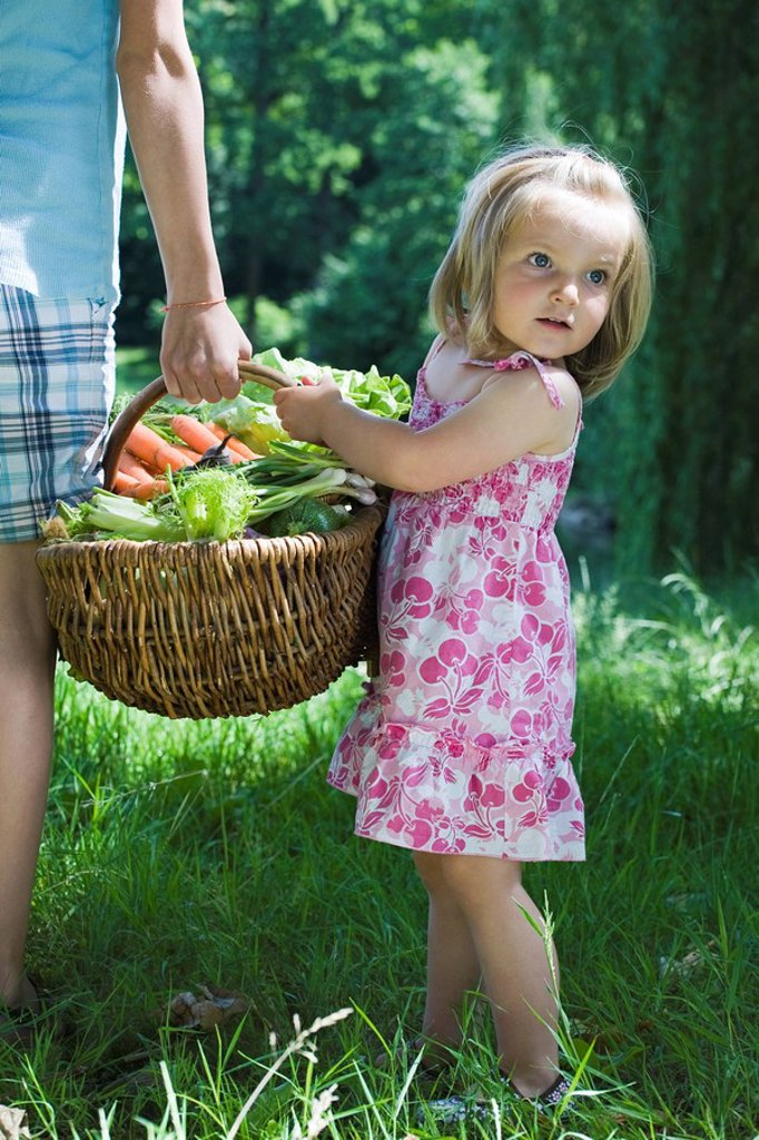 Little girl standing beside older sibling, holding large basket full of produce, cropped view : Stock Photo