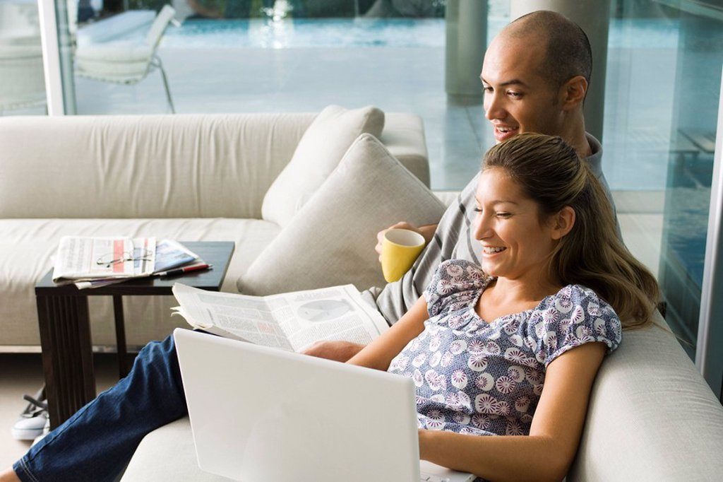 Couple sitting together on sofa, laughing at laptop computer : Stock Photo