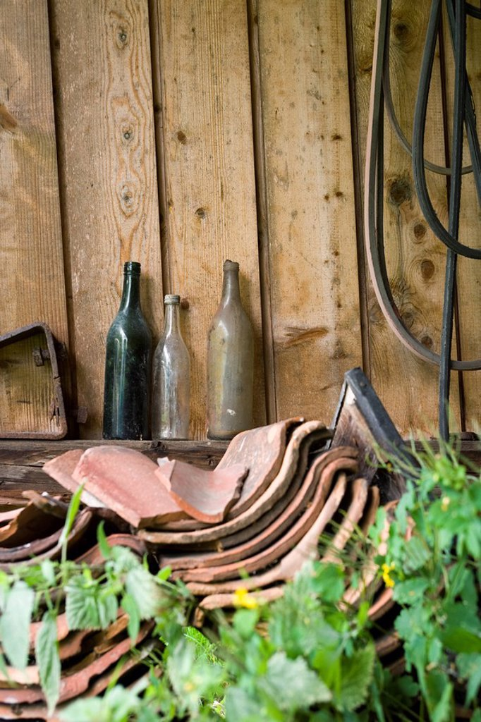Old glass bottles, broken clay tiles stacked by wall outdoors : Stock Photo