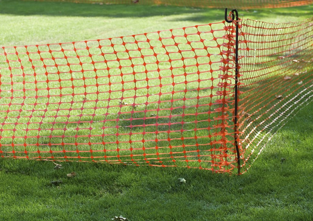 Plastic mesh fence on grass : Stock Photo