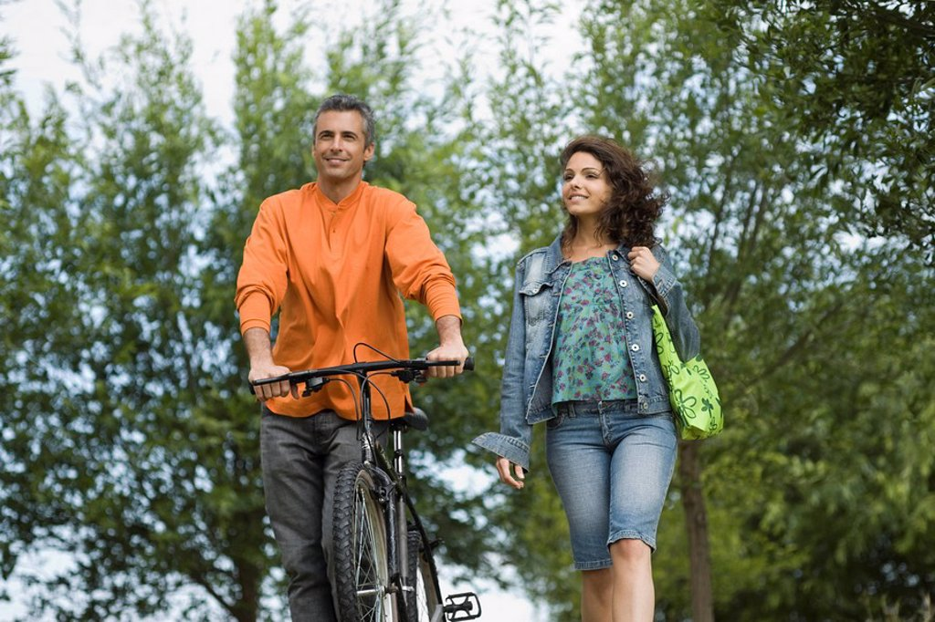 Stock Photo: 1747R-12151 Couple walking together in park, man pushing bicycle