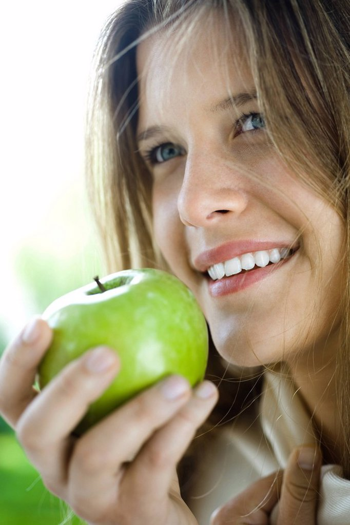 Young woman eating green apple : Stock Photo