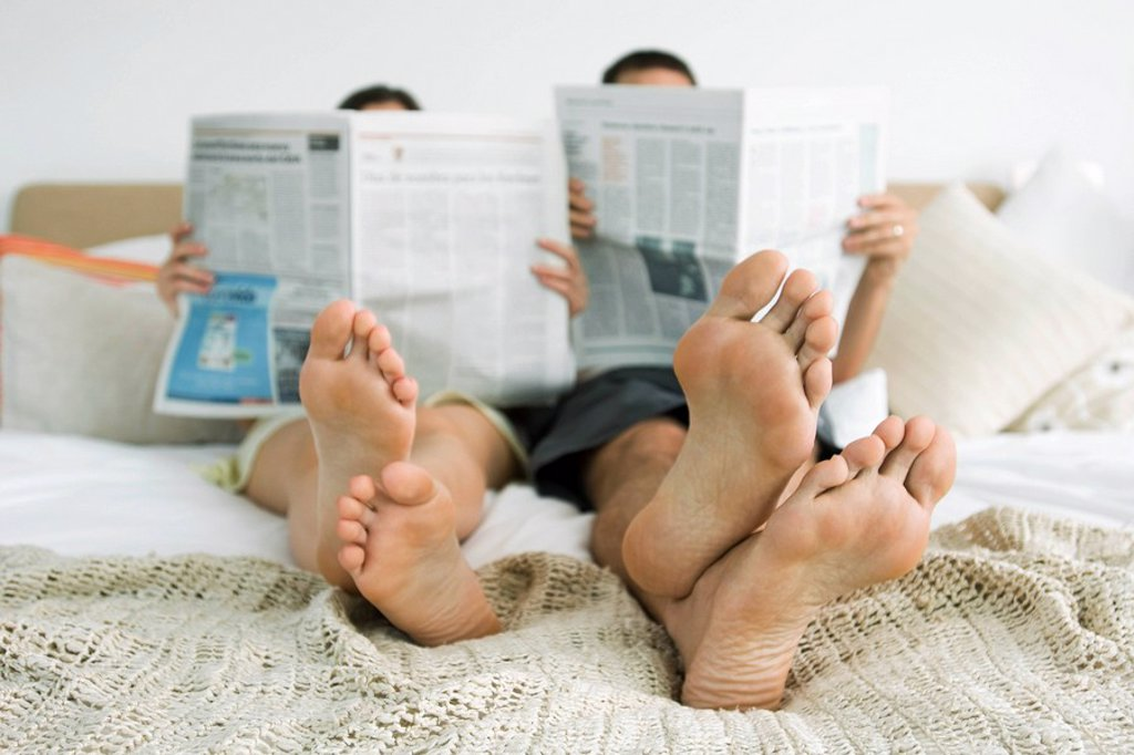 Stock Photo: 1747R-12253 Couple sitting together on bed reading newspapers