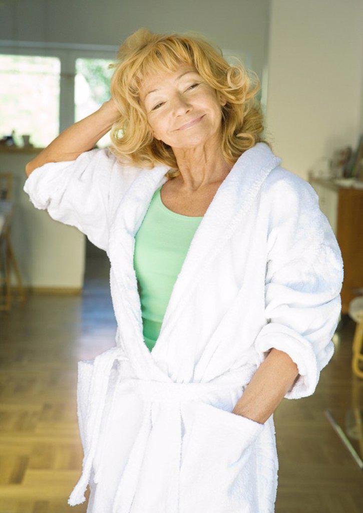 Senior woman standing in bathrobe : Stock Photo