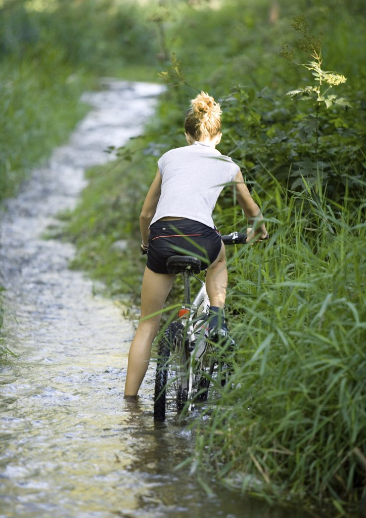 Girl on bike in stream, rear view : Stock Photo