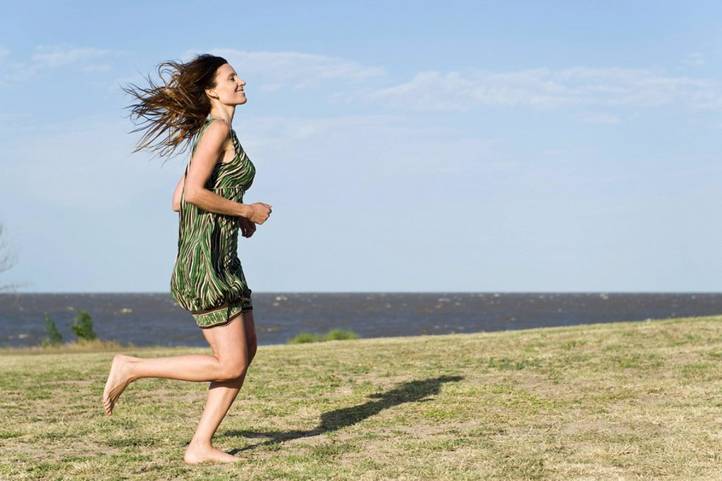 Woman in dress running across grass, barefoot : Stock Photo