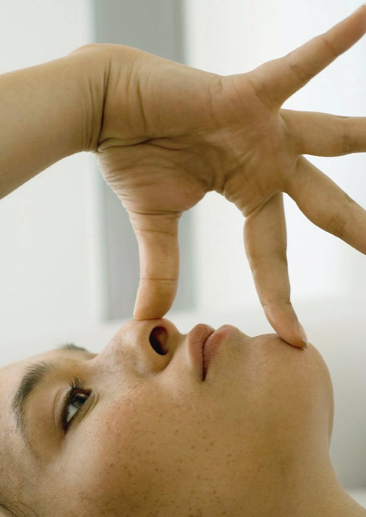 Woman with fingers on nose and chin : Stock Photo