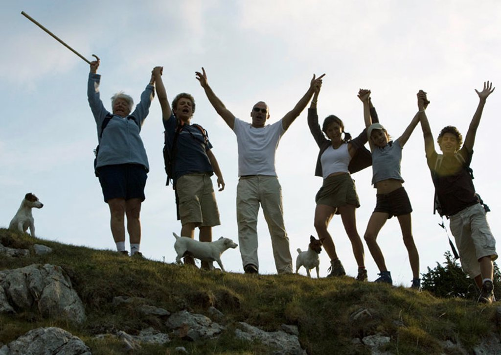 Hikers standing side by side, arms in the air : Stock Photo