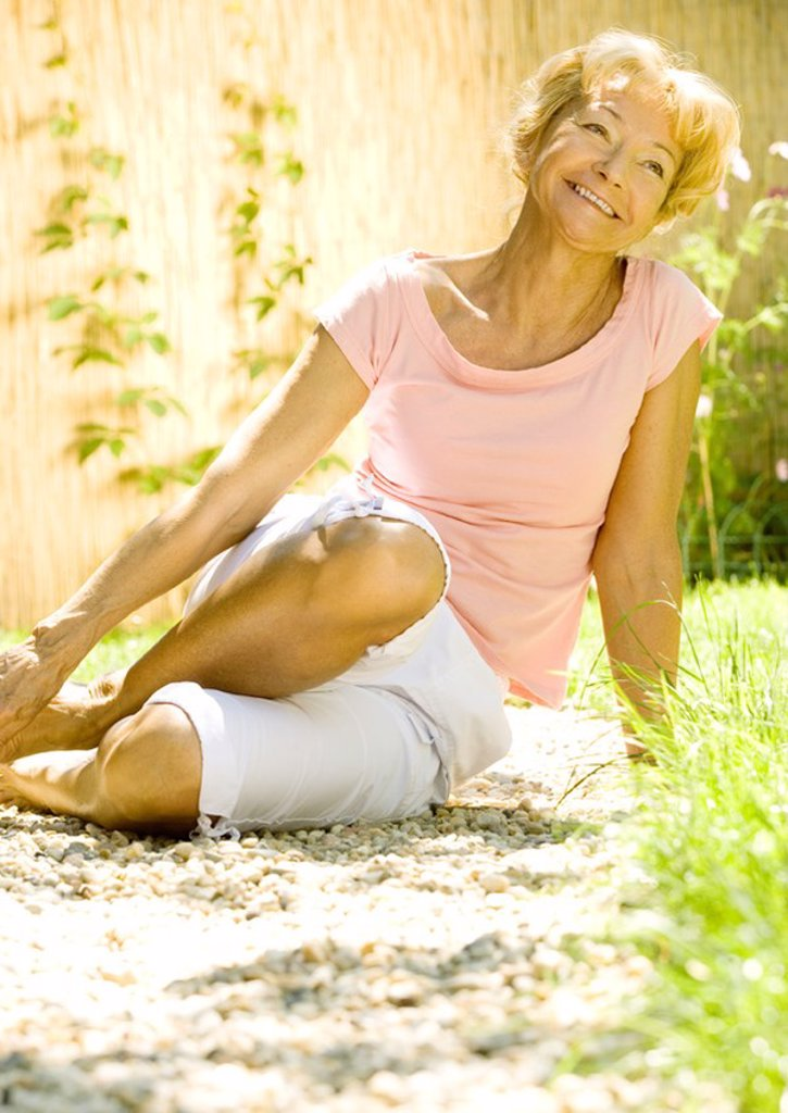 Senior woman sitting on ground outdoors, smiling : Stock Photo