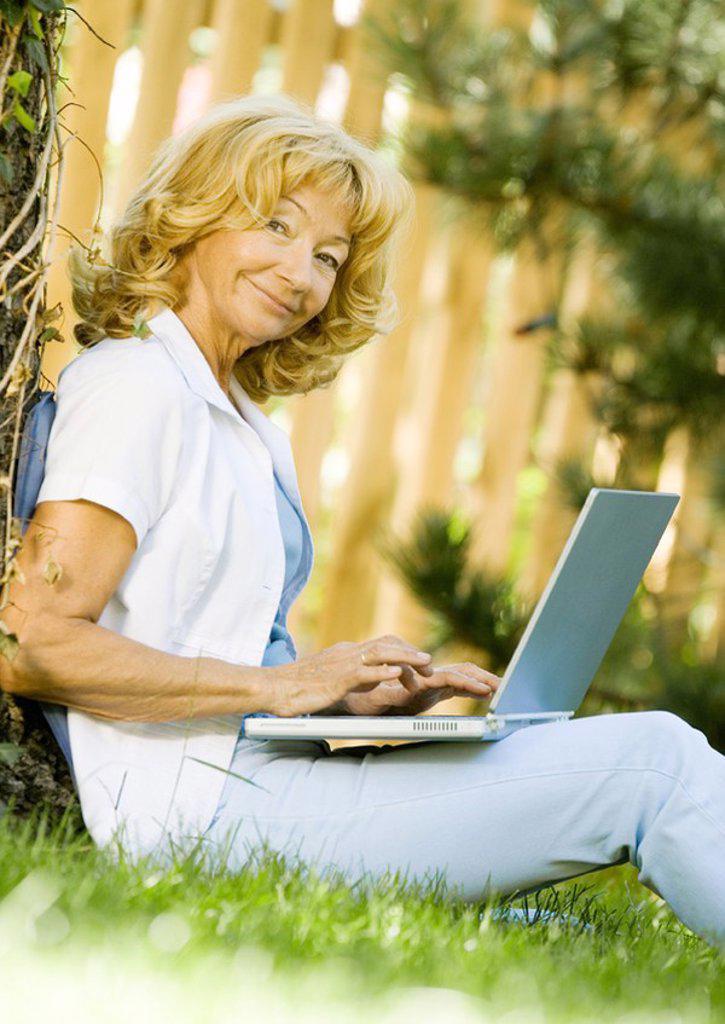 Senior woman using laptop outdoors : Stock Photo
