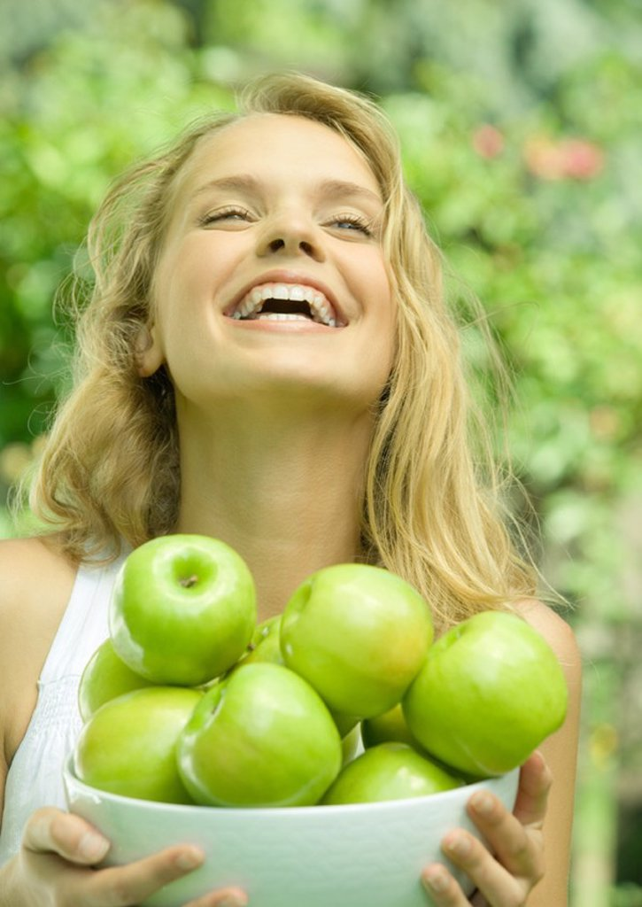 Woman holding bowl of apples, laughing : Stock Photo