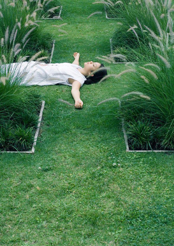 Woman lying on grass in ornamental garden : Stock Photo