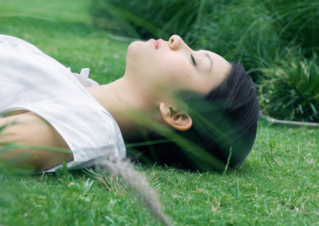 Stock Photo: 1747R-15439 Woman lying on grass in ornamental garden