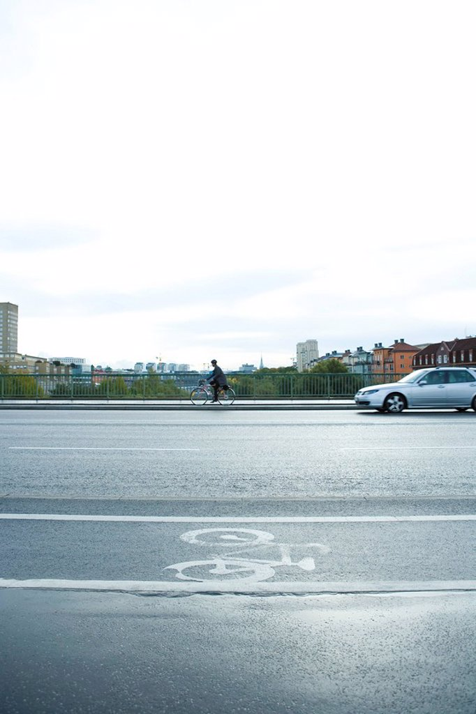 Stock Photo: 1747R-16111 Sweden, Sodermanland, Stockholm, cyclist and car sharing road