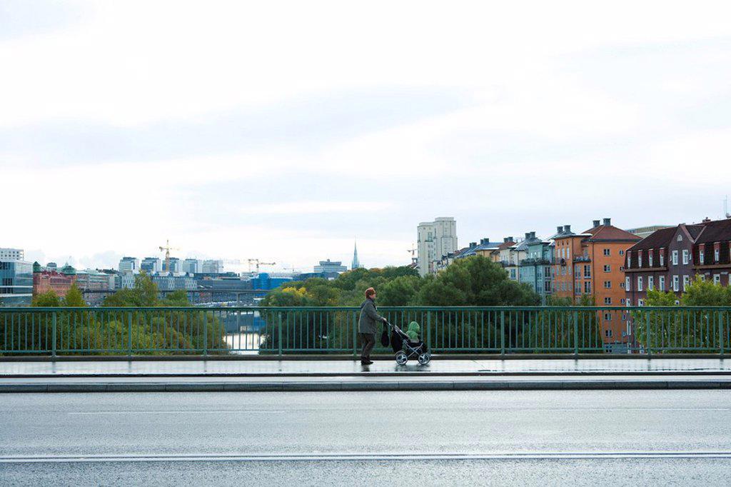 Stock Photo: 1747R-16124 Sweden, Stockholm, woman pushing baby stroller across bridge