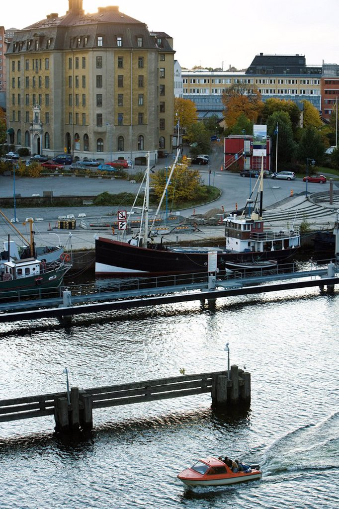 Sweden, Stockholm, small motorboat touring along waterfront : Stock Photo