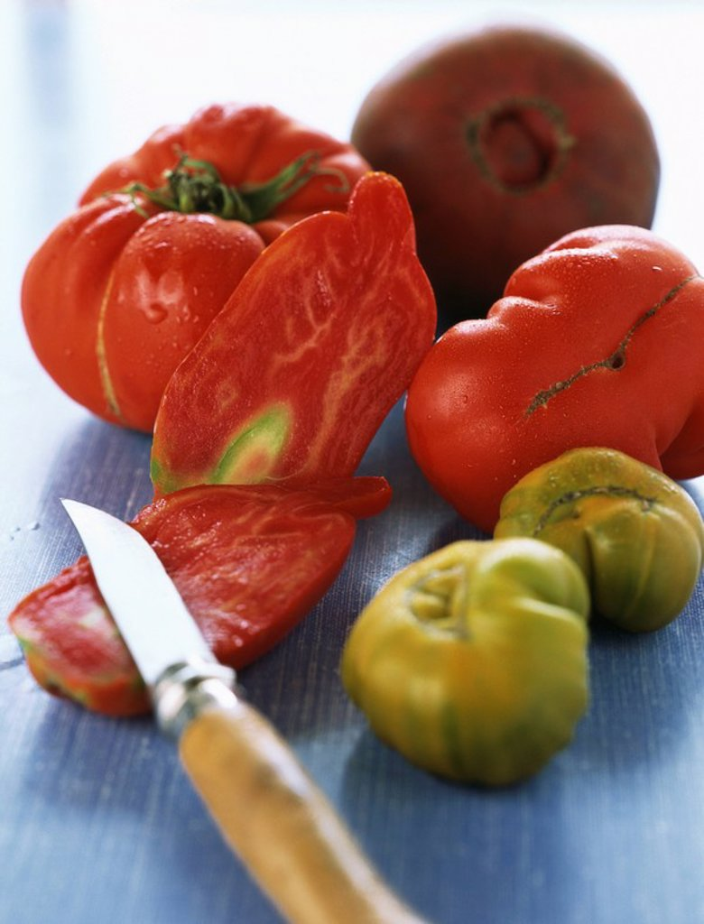 Tomatoes, one sliced with paring knife : Stock Photo