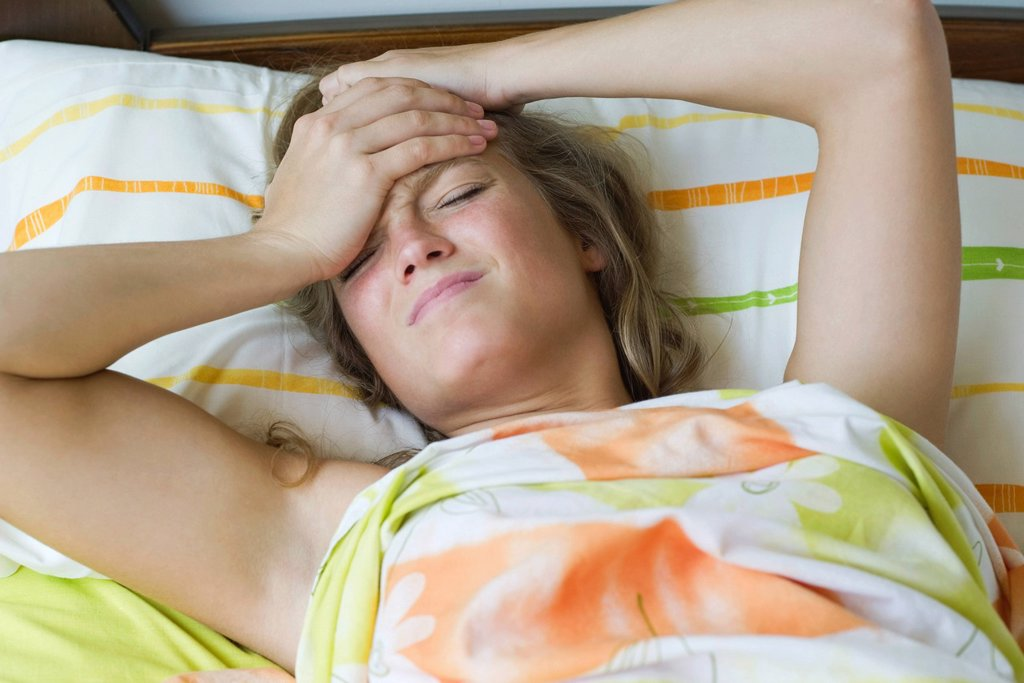 Stock Photo: 1747R-16603 Young woman lying in bed with a headache