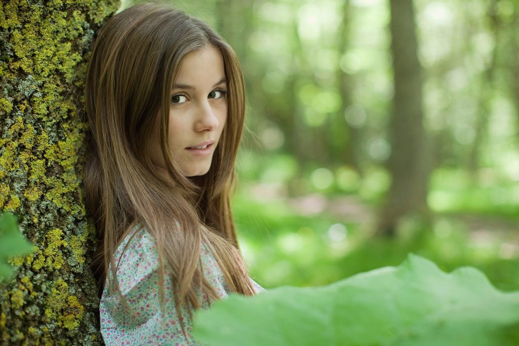 Young woman leaning against tree in woods : Stock Photo