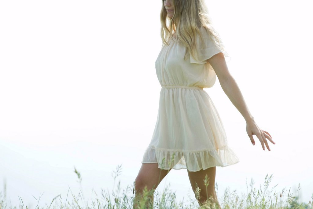 Stock Photo: 1747R-16800 Young woman walking through tall grass