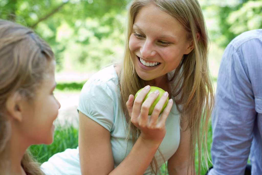 Woman enjoying picnic with her family : Stock Photo
