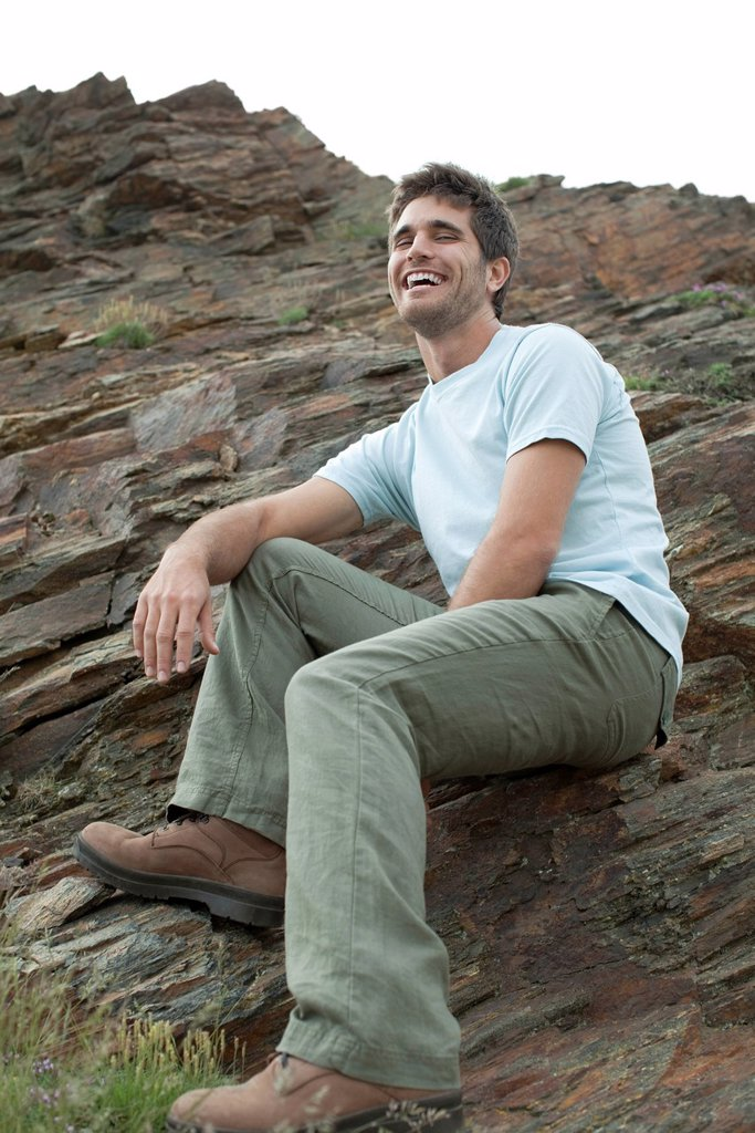 Stock Photo: 1747R-16840 Man laughing while sitting on rock, low angle view
