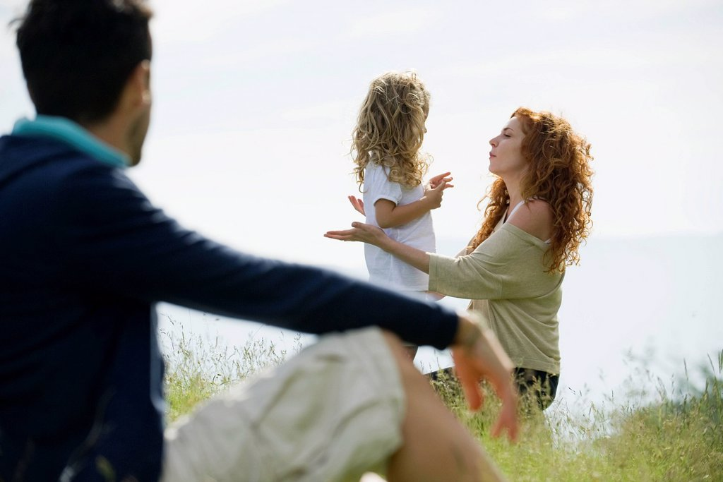 Mother talking with young daughter outdoors, father watching from foreground : Stock Photo