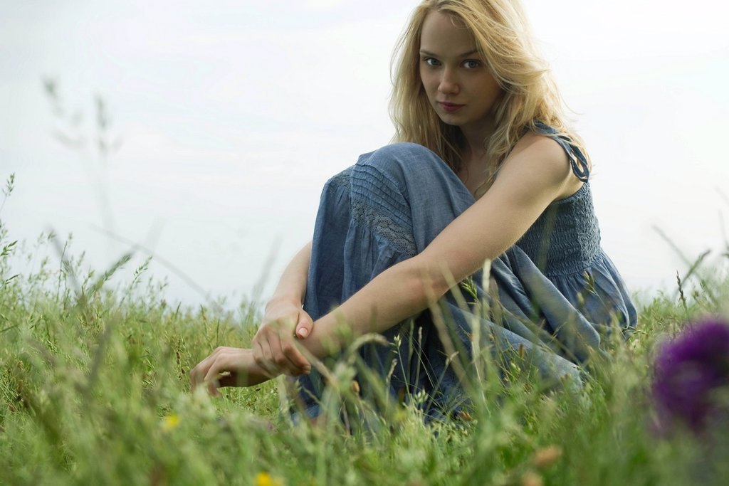 Young woman sitting in field of grass, portrait : Stock Photo