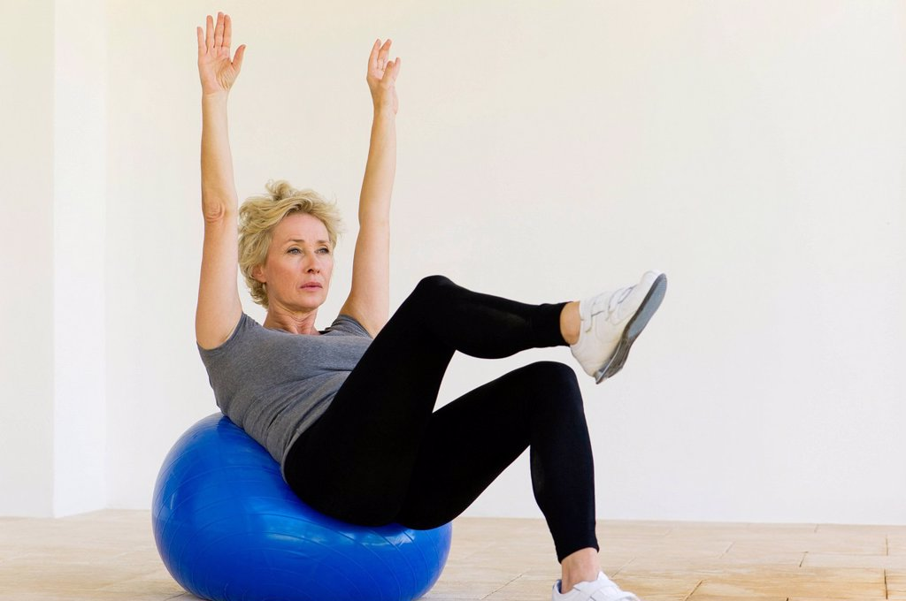 Mature woman doing pilates exercise on fitness ball : Stock Photo