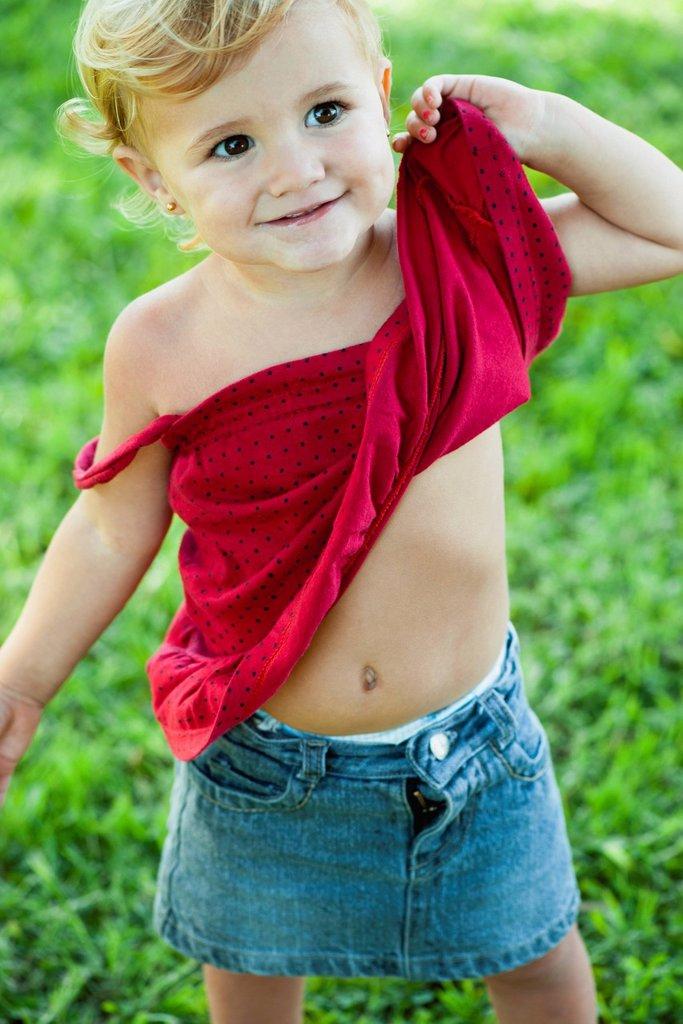Baby girl lifting shirt up, portrait : Stock Photo