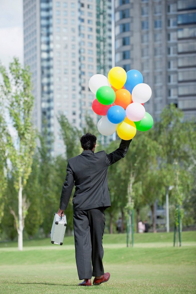 Stock Photo: 1747R-17468 Businessman walking with bunch of balloons, rear view