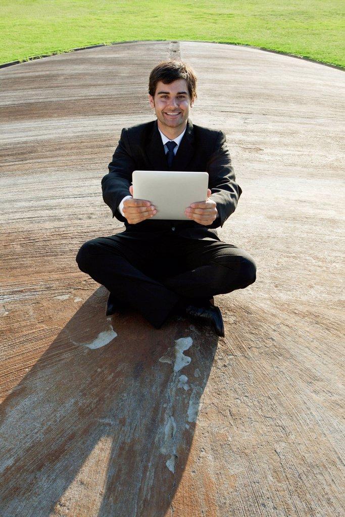 Stock Photo: 1747R-17473 Smiling young businessman with digital tablet outdoors