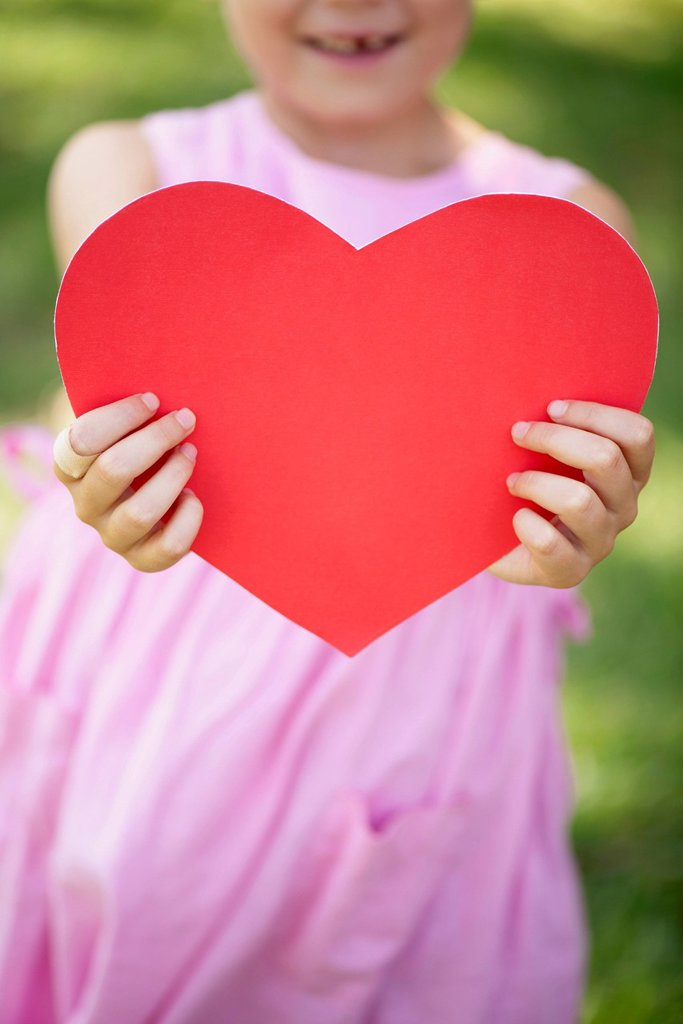 Girl holding paper heart, cropped : Stock Photo