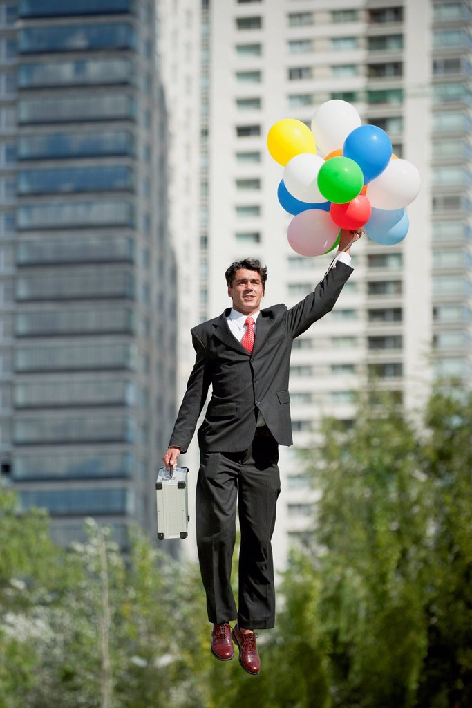 Businessman being carried away by bunch of balloons : Stock Photo