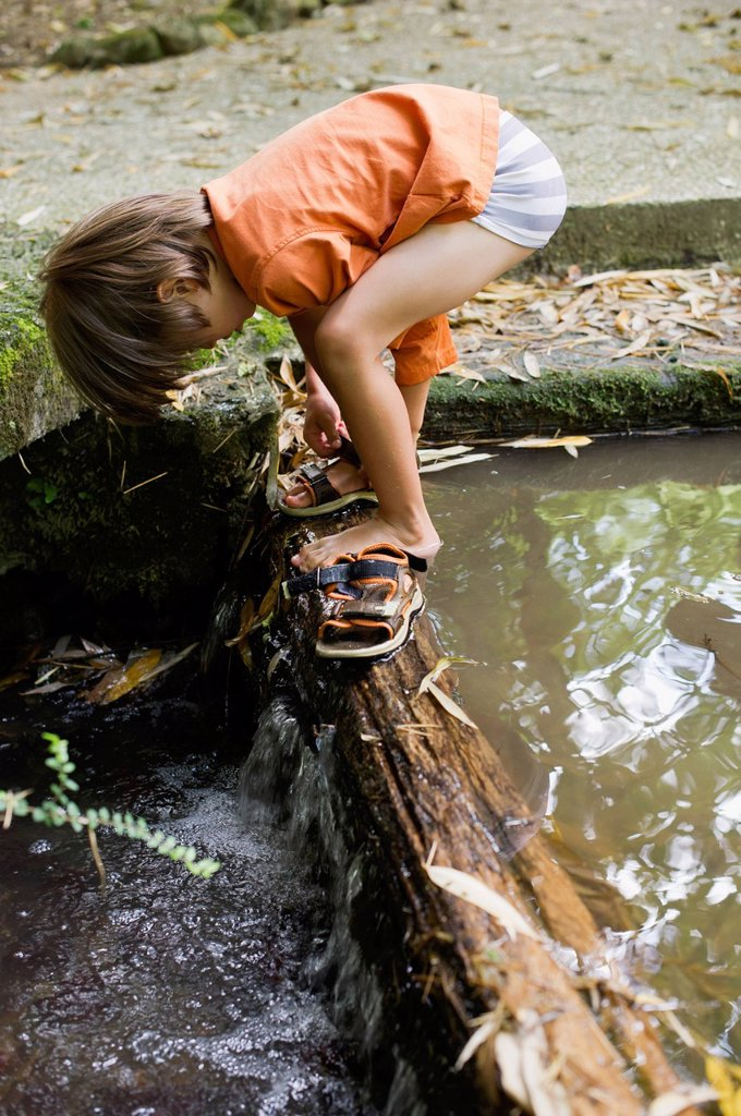 Boy putting on sandals by flowing water : Stock Photo