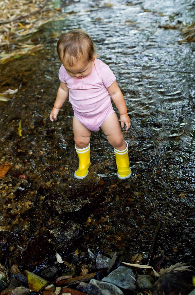 Stock Photo: 1747R-17709 Baby girl wearing rubber boots, wading in stream