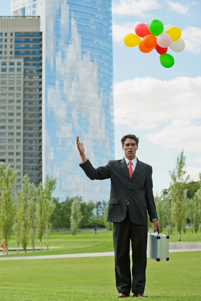 Stock Photo: 1747R-17732 Businessman releasing bunch of balloons into air, looking disappointed