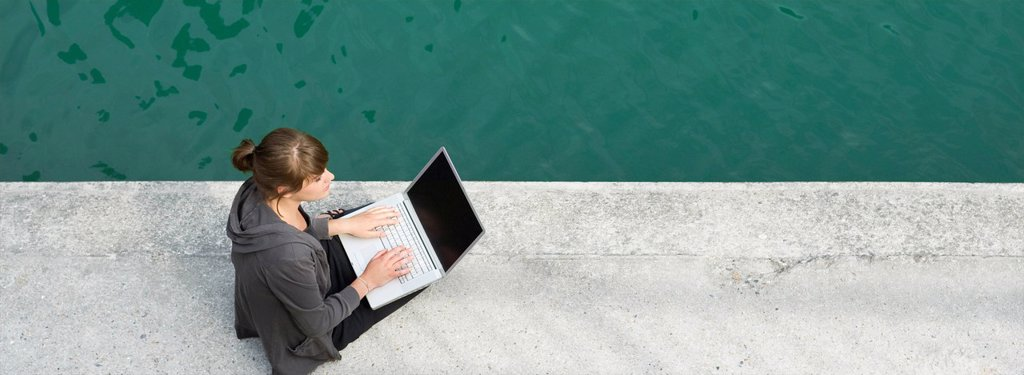 Stock Photo: 1747R-17768 Young woman sitting beside canal, using laptop computer