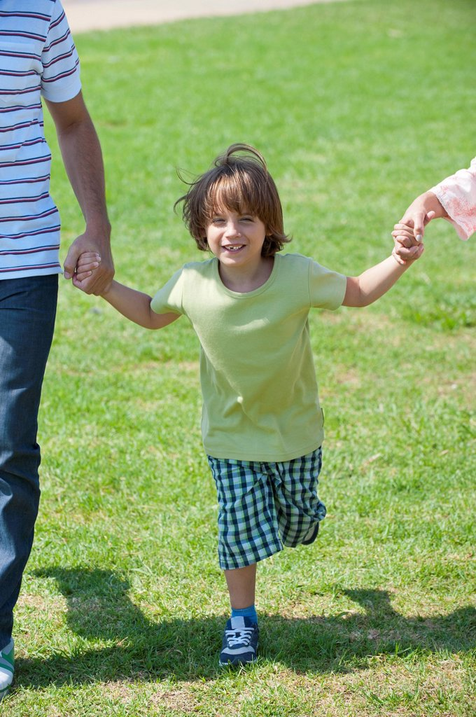 Stock Photo: 1747R-17779 Boy walking hand in hand with parents outdoors, cropped