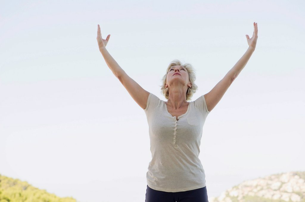 Stock Photo: 1747R-17831 Mature woman doing sun salutation