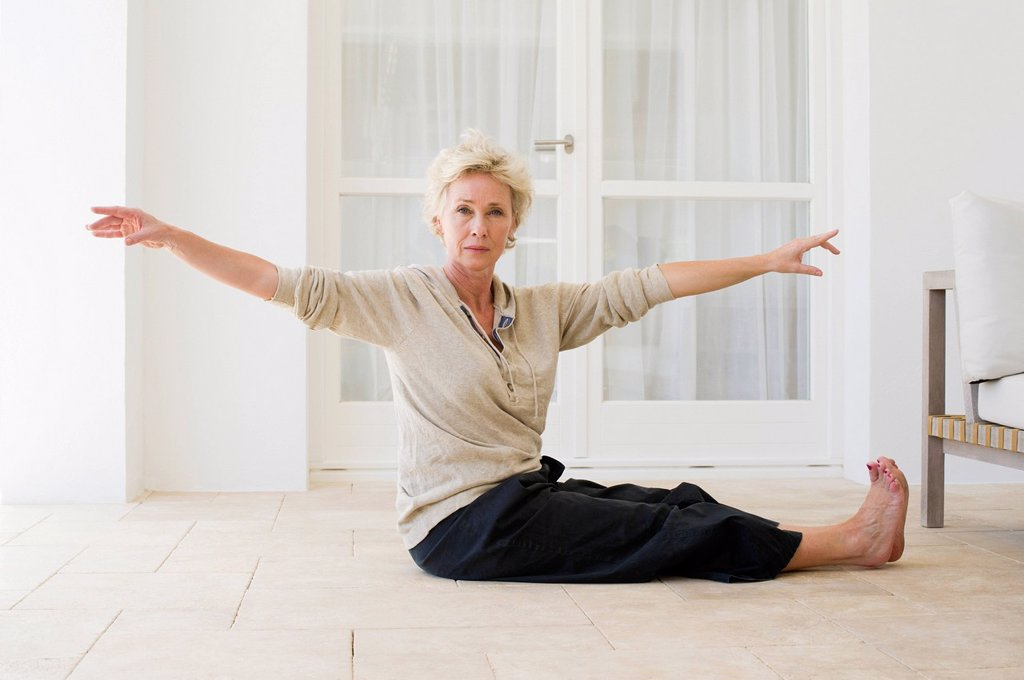 Stock Photo: 1747R-17851 Mature woman practicing yoga on floor