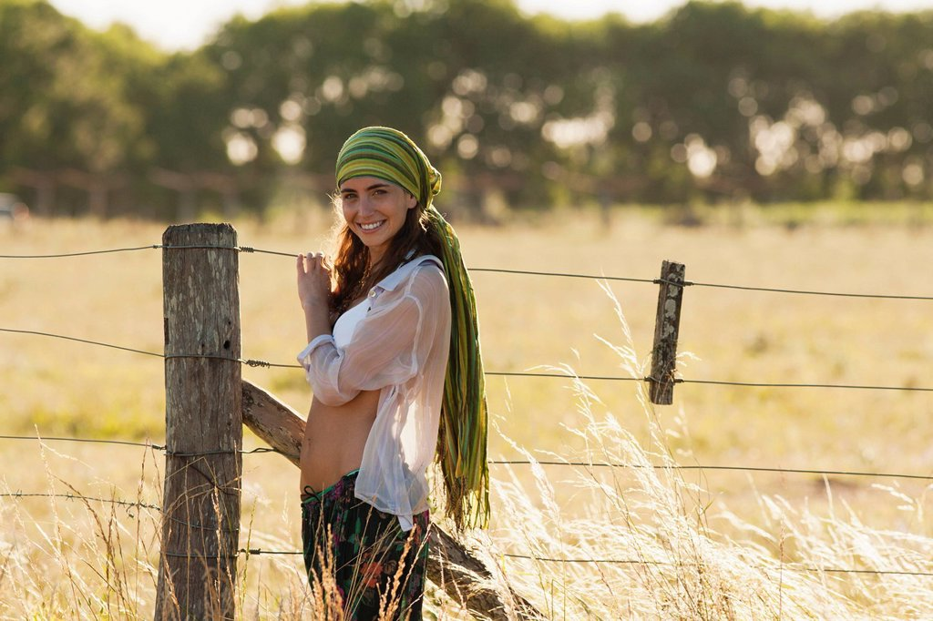 Stock Photo: 1747R-17919 Young hippie woman standing by fence in field