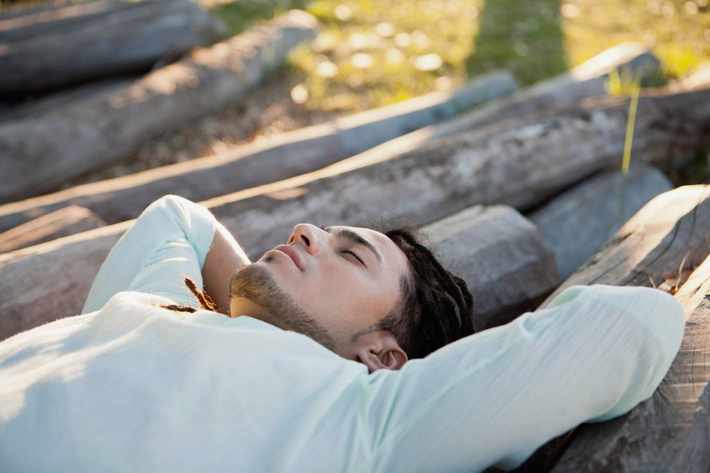 Stock Photo: 1747R-17955 Young man lying on pile of logs, eyes closed