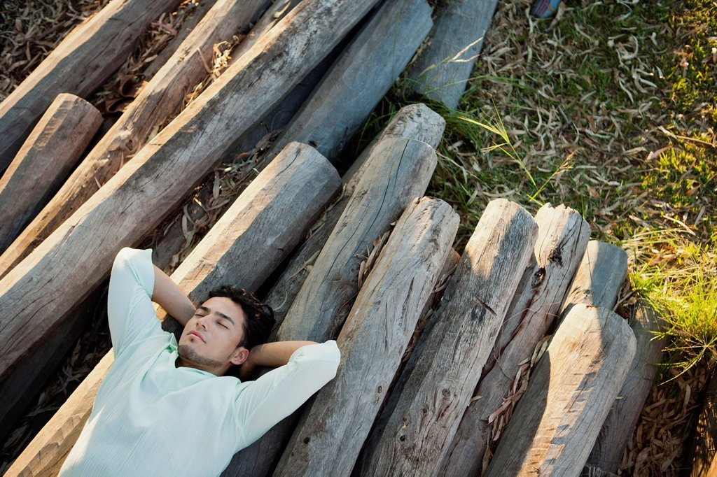 Young man lying on pile of logs, eyes closed : Stock Photo