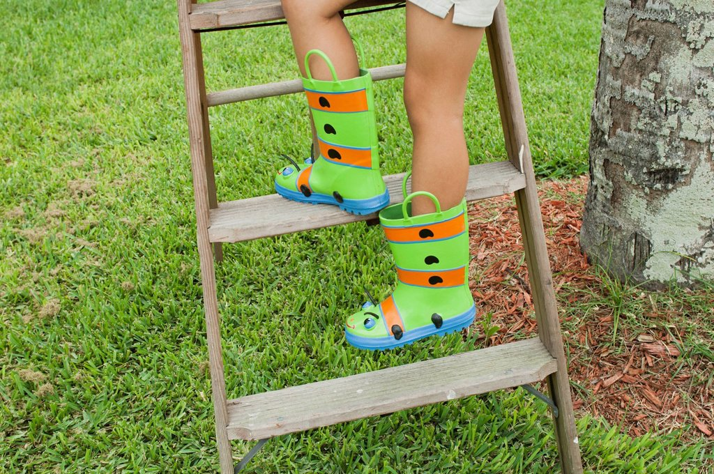 Girl wearing rubber boots, climbing ladder, cropped : Stock Photo