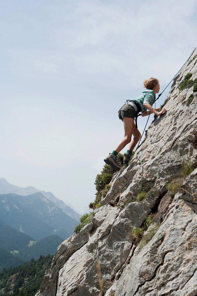 Preteen girl rock climbing : Stock Photo