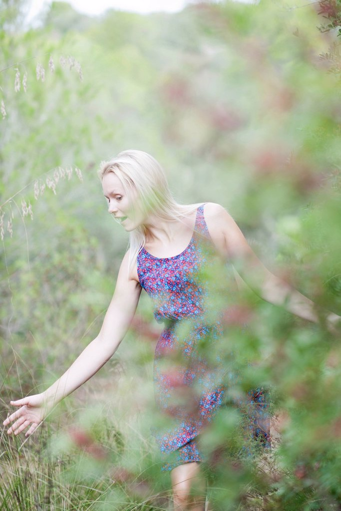 Stock Photo: 1747R-18323 Young woman walking in nature, touching tall grass