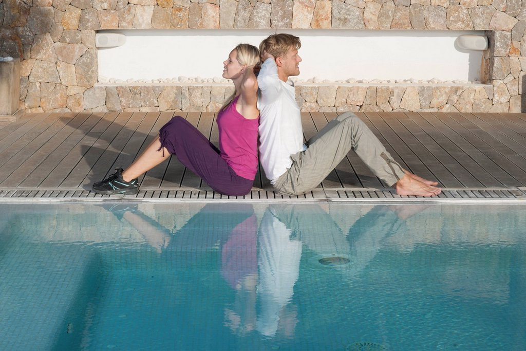 Young couple sitting back to back at poolside, hands behind heads : Stock Photo